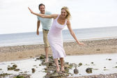 Couple at the beach walking on stones and smiling — Stock Photo
