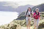 Couple on cliffside outdoors walking and smiling — Stock Photo