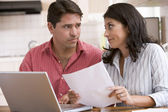 Couple in kitchen with paperwork using laptop looking unhappy — Stockfoto