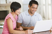Couple in dining room with laptop smiling — Stock Photo