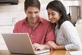 Casal na cozinha com laptop sorrindo — Fotografia Stock