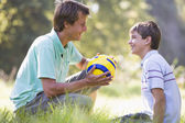 Man and young boy outdoors with soccer ball smiling — Zdjęcie stockowe