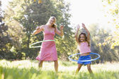 Woman and young girl with hula hoops outdoors smiling — Stock Photo