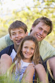 Man with two children sitting outdoors smiling — Stock Photo