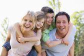 Couple giving two young children piggyback rides smiling — Stock Photo