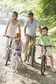 Family sitting on bikes on path smiling — Stock Photo