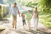 Familie running outdoors holding hands and smiling — Stockfoto