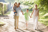 Family walking outdoors holding hands and smiling — Стоковое фото