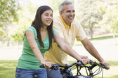Man and girl on bikes outdoors smiling — Stok fotoğraf