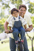 Man and young boy on a bike outdoors smiling — Stok fotoğraf