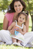 Woman and young girl sitting outdoors with toy smiling — Stock Photo