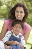 Woman and young boy sitting outdoors smiling — Stock Photo