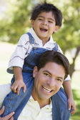 Man giving young boy shoulder ride outdoors smiling — Stock Photo