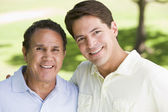 Two men standing outdoors smiling — Stock Photo