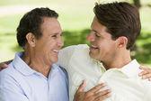 Twee mannen permanent buitenshuis verlijmen en glimlachen — Stockfoto
