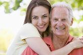 Homem e mulher outdoor abraçando e sorrindo — Foto Stock