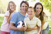 Family standing outdoors holding volleyball smiling — Stock Photo