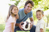 Man and two young children outdoors holding volleyball and smili — Stock Photo