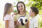 Woman and two young children outdoors holding volleyball and smi — Stock Photo