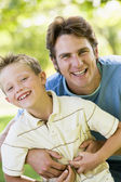 Man and young boy outdoors embracing and smiling — Stock Photo