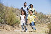 Family running on path smiling — Foto de Stock