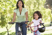 Woman and young girl on bikes outdoors smiling — Stock Photo