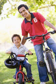 Man and young boy on bikes outdoors smiling — Stock Photo