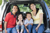 Family sitting in back of van smiling — Stok fotoğraf