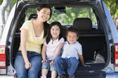 Woman with two children sitting in back of van smiling — Stock Photo