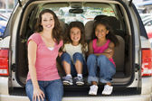 Woman with two young girls sitting in back of van smiling — Stock Photo