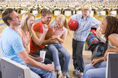 Family in bowling alley with two friends cheering and smiling — Stock Photo