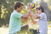 Man and young boy outdoors holding soccer ball and smiling — Stock Photo