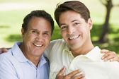 Dos hombres abrazándose al aire libre y sonriendo — Foto de Stock