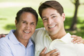 Two men outdoors embracing and smiling — Stock Photo
