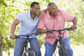 Two men on bikes outdoors smiling — Stock Photo