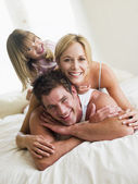 Family in bed playing and smiling — Stock Photo