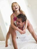 Muž a mladá holka v posteli, hraje a usmívá se — Stock fotografie