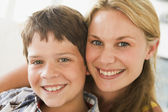Woman and young boy in living room smiling — Stock Photo