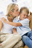 Woman kissing disgusted young boy in living room — Stock Photo