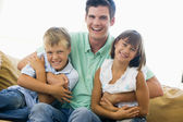 Man and two young children in living room smiling — Foto Stock