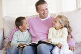 Man and two children sitting in living room reading book and smi — Stok fotoğraf