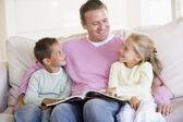 Man en twee kinderen zitten in woonkamer lezen van boek en smi — Stockfoto