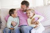 Człowiek i dwoje dzieci siedząc w salonie uśmiechający się — Zdjęcie stockowe