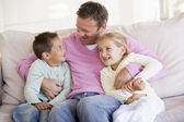 Man and two children sitting in living room smiling — Stock Photo