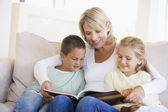 Woman and two children sitting in living room reading book and s — Stock Photo