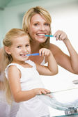 Woman and young girl in bathroom brushing teeth — Stock Photo