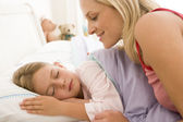 Woman waking young girl in bed smiling — Stock Photo