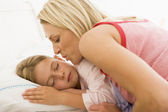 Woman waking young girl in bed with a kiss — Stock Photo