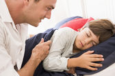 Man waking young boy in bed smiling — Stock Photo