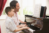 Man and young boy playing piano and smiling — Stock Photo